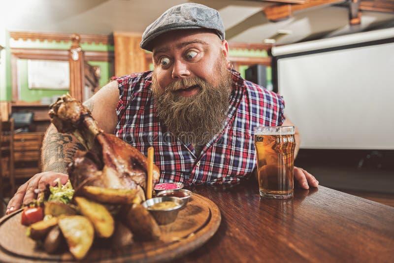 Tipo obeso sorpreso che guarda fisso all'alimento non sano immagine stock