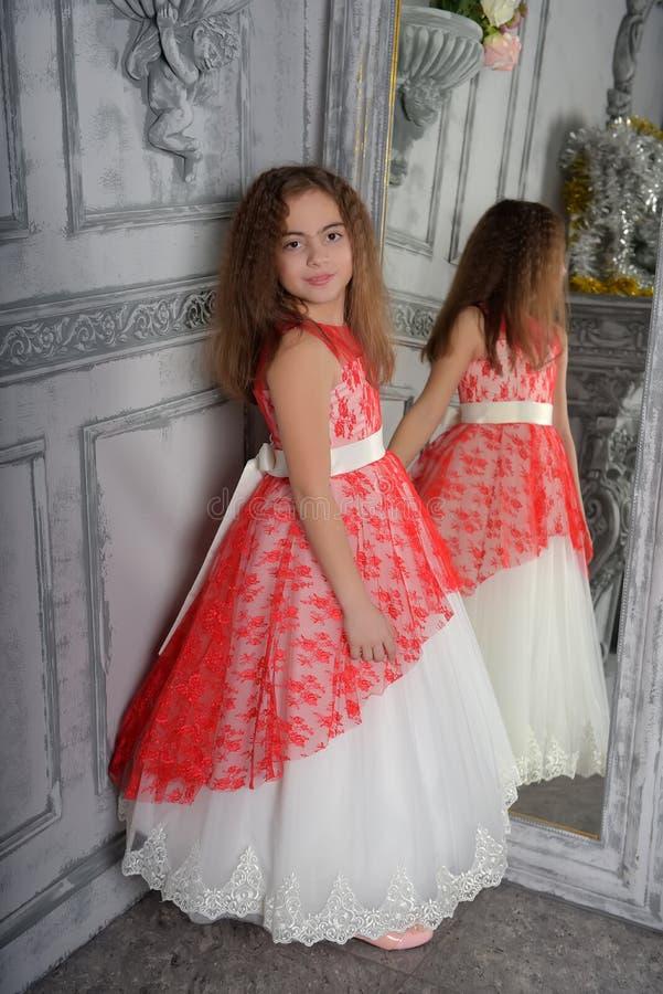 Tipo orientale la ragazza il castana nel bianco con un vestito elegante rosso fotografie stock