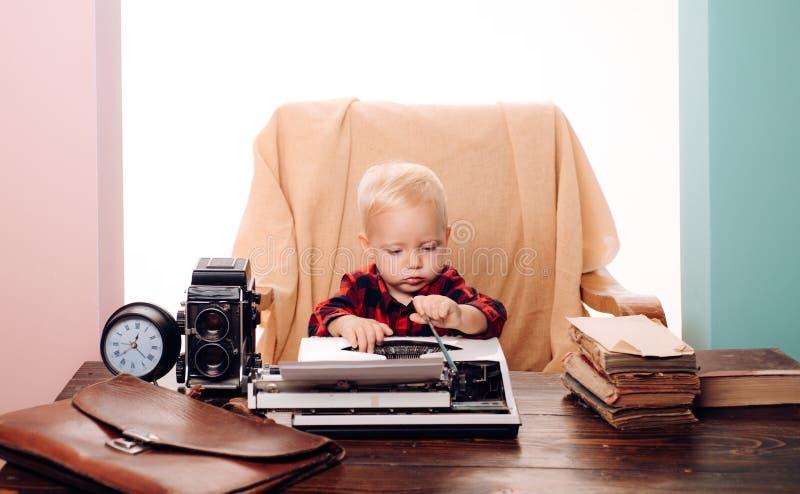 Tipo papel de la secretaria del niño pequeño en la máquina de escribir vieja en el escritorio El niño aprende mecanografiar en la fotografía de archivo