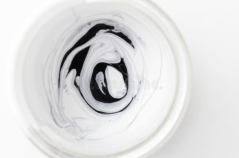 Tipo preto e branco da pintura misturado no frasco de vidro, vista superior foto de stock