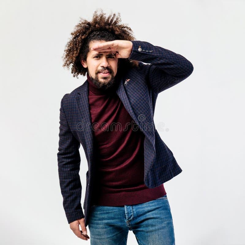 Tipo riccio alla moda con una barba vestita nel collo alto di Borgogna, in rivestimento a quadretti grigio e nelle pose dei jeans fotografia stock libera da diritti