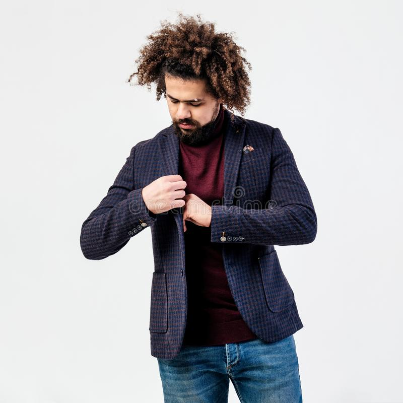Tipo riccio alla moda con una barba vestita nel collo alto di Borgogna, in rivestimento a quadretti grigio e nelle pose dei jeans fotografia stock