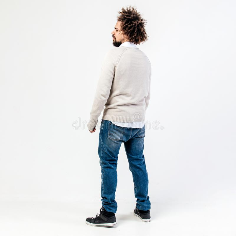 Tipo riccio castano alla moda con una barba vestita in saltatore beige sopra una camicia bianca e nelle pose dei jeans nello stud immagine stock