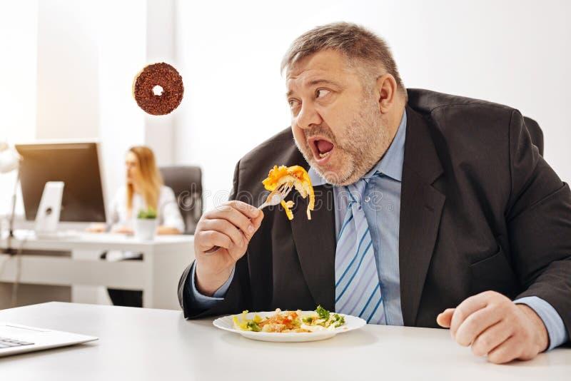 Tipo rotondetto divertente che desidera mangiare alcune ciambelle fotografie stock libere da diritti