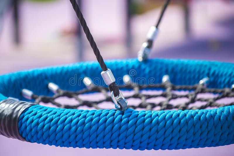 Tipo rotondo blu nido dell'oscillazione sul campo da giuoco Il concetto di ricreazione di sport per i bambini e gli adolescenti,  fotografie stock libere da diritti