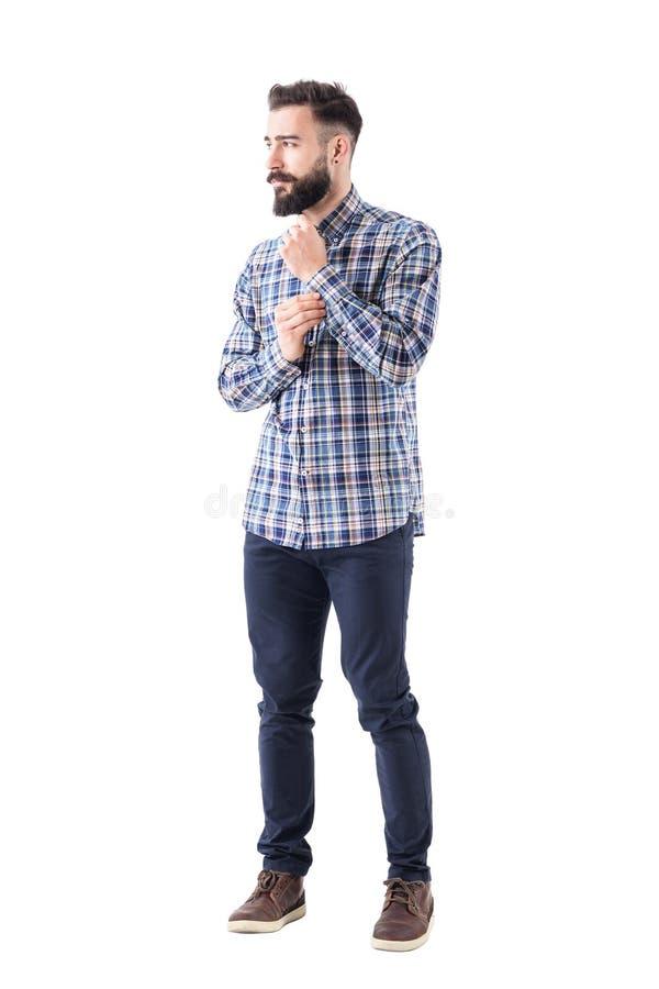 Tipo sicuro barbuto fresco che si veste abbottonando il bottone della manica e distogliendo lo sguardo meditatamente fotografia stock