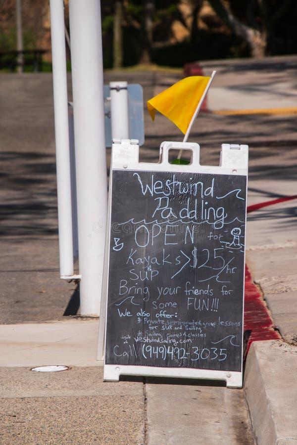 Tipo sinal da placa de sanduíche de rua que anuncia um remo e um negócio alugado do caiaque imagens de stock