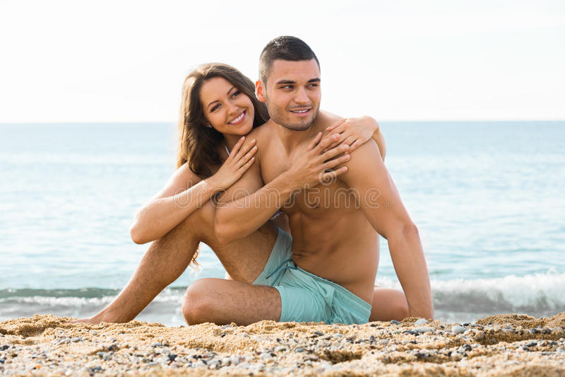 Tipo sorridente e la sua amica sulla spiaggia di sabbia fotografia stock