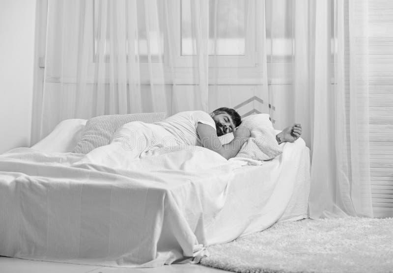 Tipo sul fronte calmo che dorme sugli strati bianchi, cuscino Equipaggi mettere sul letto, coperto di coperta, tende bianche su f fotografia stock