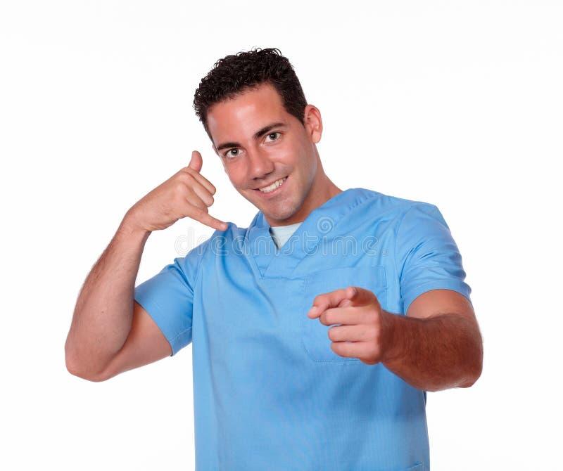 Tipo sveglio dell'infermiere con indicare di gesto di chiamata immagine stock libera da diritti