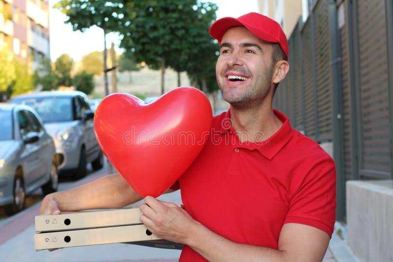 Tipo sveglio di consegna della pizza che tiene le pizze ed il pallone a forma di del cuore immagine stock