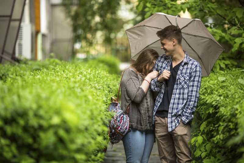 Tipo sveglio e ragazza che parlano sotto un ombrello Amore fotografia stock libera da diritti