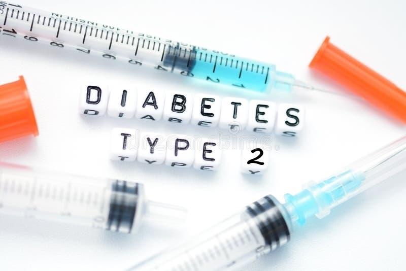 Tipo - texto de la diabetes 2 deletreado con las gotas plásticas de la letra colocadas al lado de una jeringuilla de la insulina imagenes de archivo