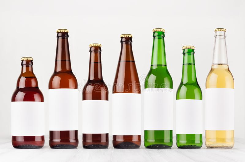 Tipo y colores de la colección de las botellas de cerveza el diversos con la etiqueta blanca en blanco en el tablero de madera bl foto de archivo libre de regalías
