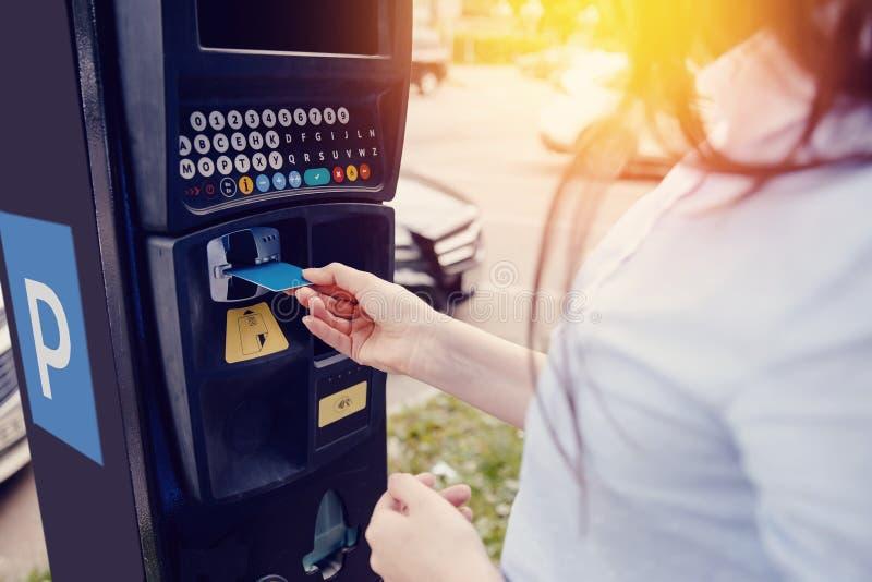 Tipos da menina o texto com suas mãos para fazer para fora o bilhete para o estacionamento e o pagamento de estacionamento da máq fotos de stock