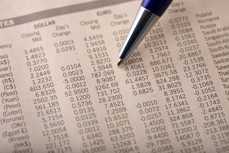 Tipos de cambio de dinero en circulación en periódico financiero fotos de archivo