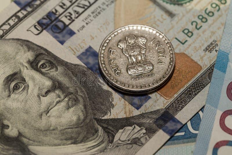 Tipos de cambio El ratio del dólar a la rupia india El nuevo billete de banco es cientos dólares Moneda india cinco rupias fotos de archivo libres de regalías