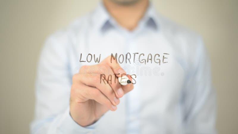 Tipos de préstamo hipotecario bajos, escritura del hombre en la pantalla transparente foto de archivo libre de regalías