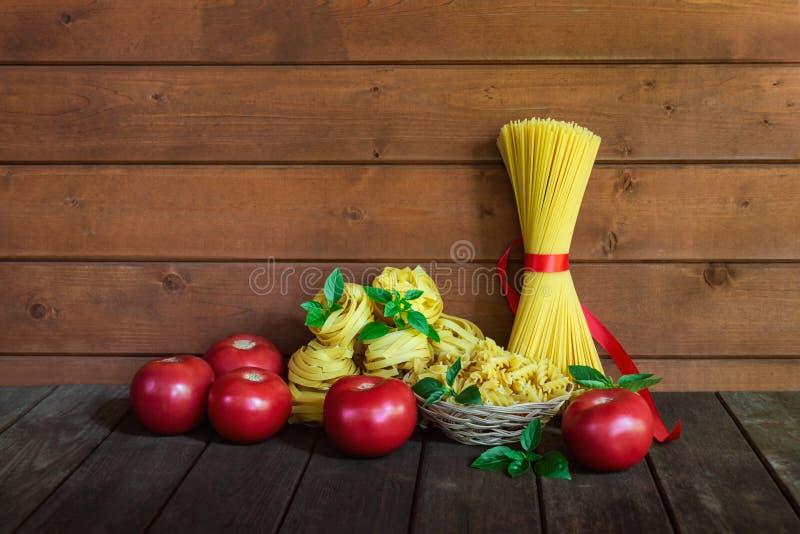 Tipos diferentes da massa crua, de tomates maduros vermelhos e das folhas verdes da manjericão Vista com espa?o da c?pia imagens de stock royalty free