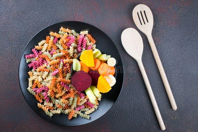 Tipos diferentes da massa italiana crua colorida e de suas tinturas vegetais naturais aipo, beterraba, cenoura, abóbora, pastinag imagem de stock