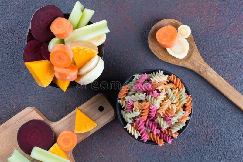 Tipos diferentes da massa italiana crua colorida e de suas tinturas vegetais naturais aipo, beterraba, cenoura, abóbora, pastinag fotos de stock