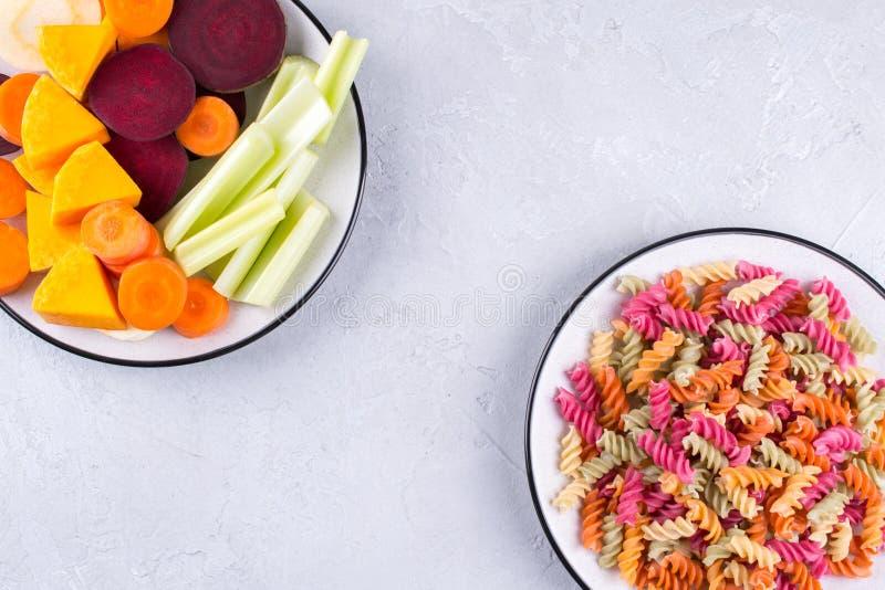 Tipos diferentes da massa italiana crua colorida e de suas tinturas vegetais naturais aipo, beterraba, cenoura, abóbora, pastinag imagens de stock