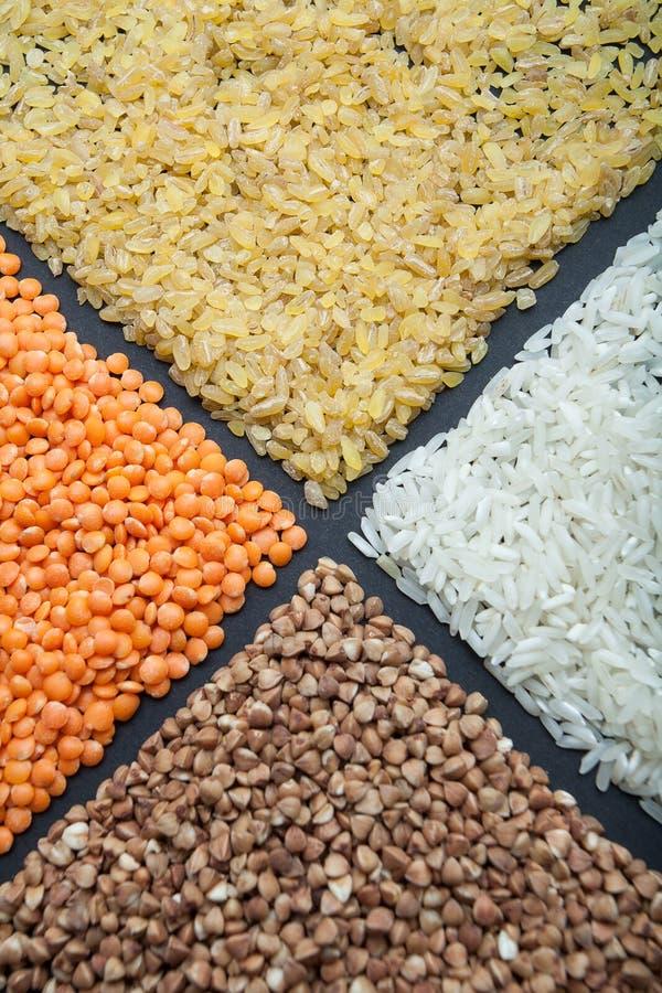 Tipos diferentes de cereais e de grãos-de-bico das leguminosa, lentilhas vermelhas, trigo mourisco, arroz em um fundo preto fotos de stock royalty free