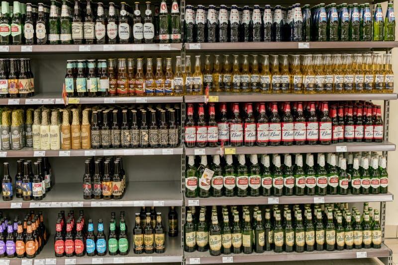 Tipos diferentes de cerveja nas prateleiras no supermercado fotografia de stock