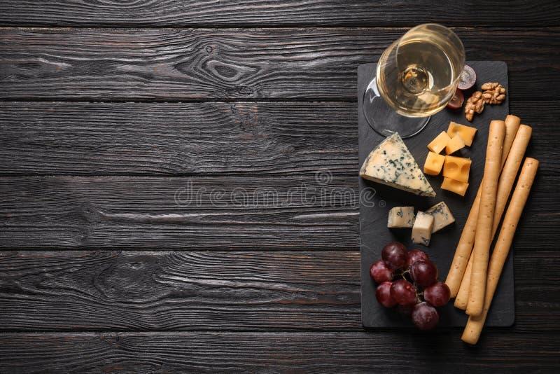 Tipos diferentes de queijo delicioso servidos na tabela de madeira preta, vista superior Espa?o para fotografia de stock