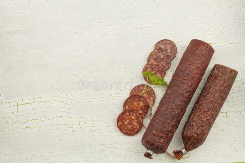 Tipos diferentes do salame picante em fundo sombreado rachado fotos de stock royalty free