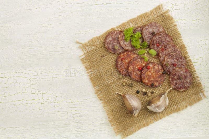 Tipos diferentes do salame picante em fundo sombreado rachado fotografia de stock royalty free