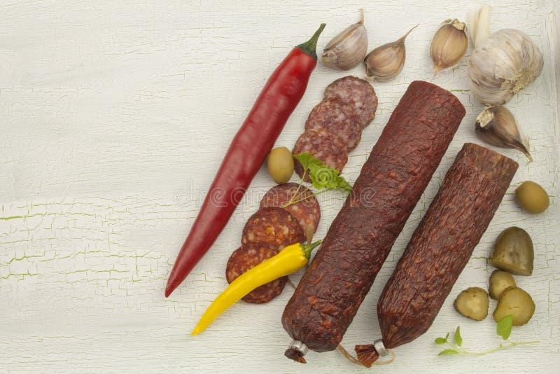 Tipos diferentes do salame picante em fundo sombreado rachado imagens de stock