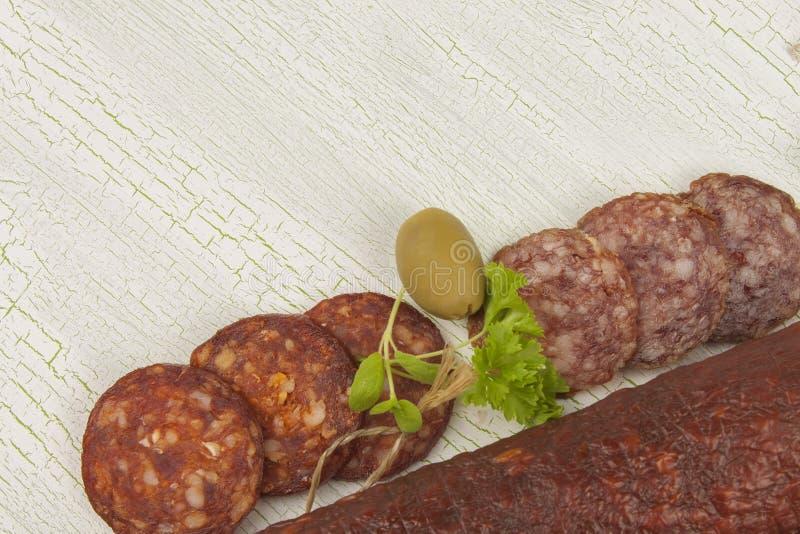 Tipos diferentes do salame picante em fundo sombreado rachado imagem de stock royalty free