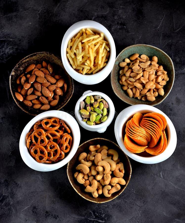 Tipos diferentes dos petiscos - microplaquetas, amendoins salgados, cajus, amêndoas e pistaches, pretzeis com sal, batatas, palha imagens de stock royalty free