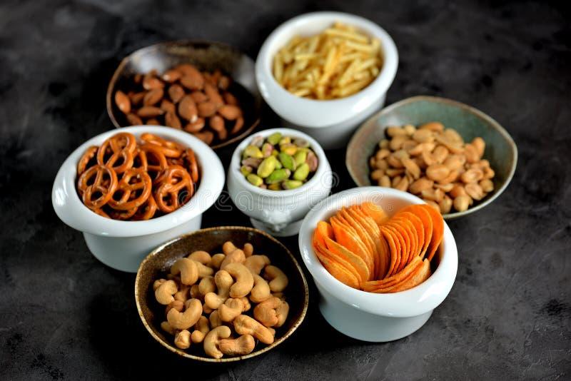 Tipos diferentes dos petiscos - microplaquetas, amendoins salgados, cajus, amêndoas e pistaches, pretzeis com sal, batatas, palha fotos de stock