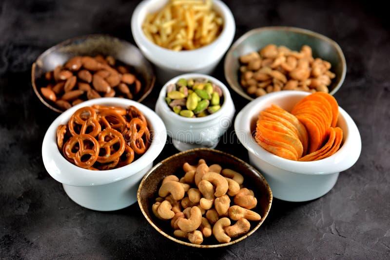 Tipos diferentes dos petiscos - microplaquetas, amendoins salgados, cajus, amêndoas e pistaches, pretzeis com sal, batatas, palha fotos de stock royalty free