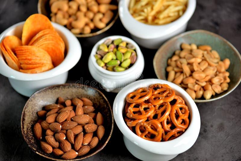 Tipos diferentes dos petiscos - microplaquetas, amendoins salgados, cajus, amêndoas e pistaches, pretzeis com sal, batatas, palha imagem de stock