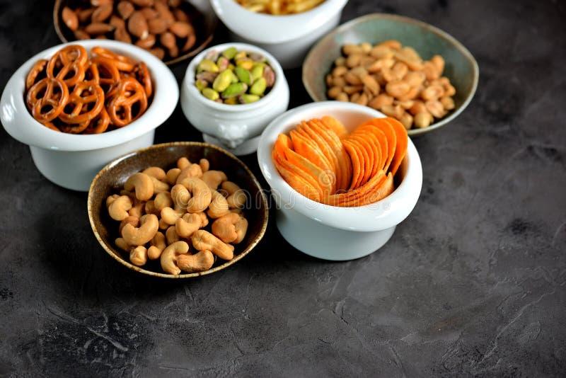 Tipos diferentes dos petiscos - microplaquetas, amendoins salgados, cajus, amêndoas e pistaches, pretzeis com sal, batatas, palha fotografia de stock royalty free