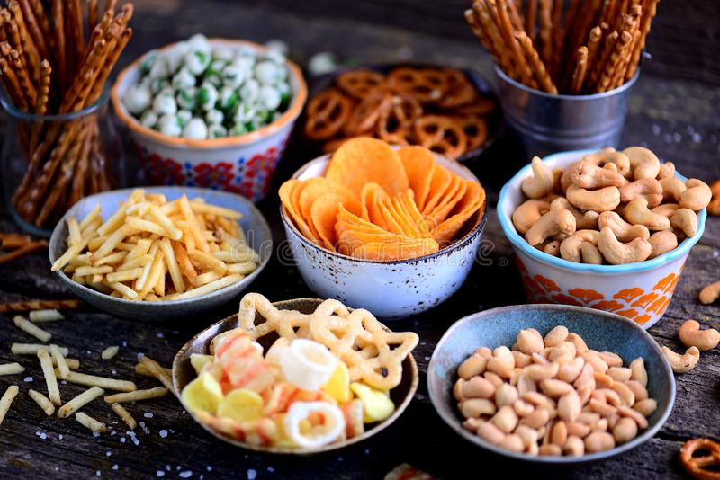 Tipos diferentes dos petiscos - microplaquetas, amendoins salgados, cajus, ervilhas com wasabi, pretzeis com sal, batatas, palha  imagem de stock royalty free