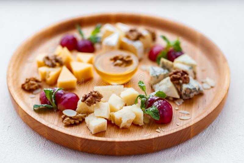 Tipos diferentes dos queijos na bandeja de madeira fotografia de stock