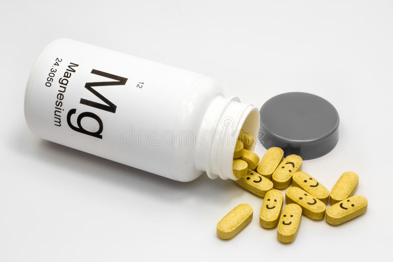 Tipped over bottle of Magnesium vitamins. A tipped over white bottle of yellow magnesium vitamin pills against a white background. Some of the pills have happy royalty free stock photos