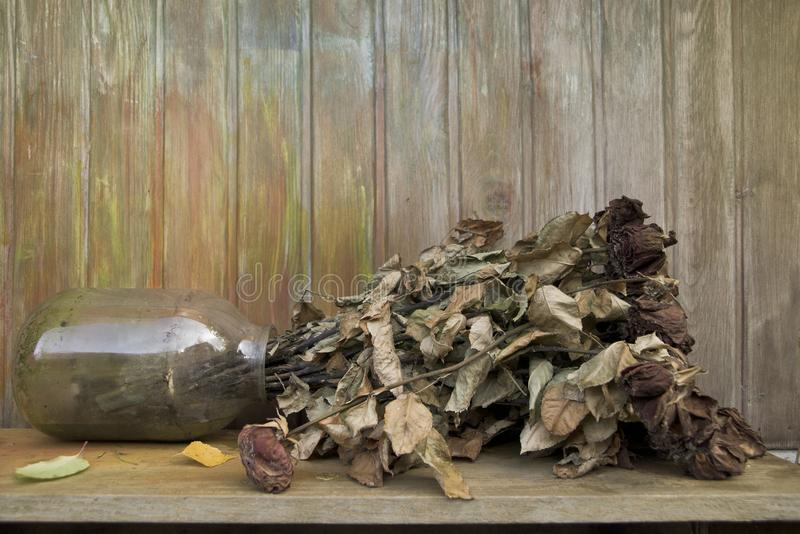 Jar Of Dead Flowers. Tipped over jar of dead flowers, outdoor shot stock photos