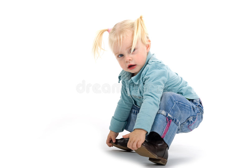 Tipping Over. Little blond haired girl crouched down to grab the front of her shoes, starting to fall over into a sitting position. Unsure expression. Taken in stock image