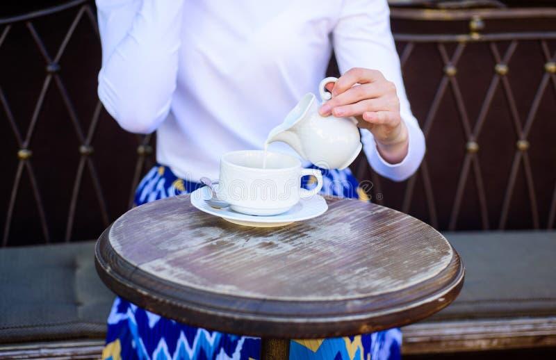 Tipps für das gesündere Kaffeetrinken Übergeben Sie die Frau, die draußen auslaufende Milch Caféterrasse des schwarzen Kaffees, A lizenzfreie stockfotos