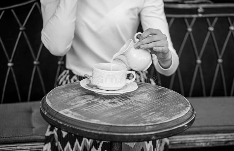 Tipps für das gesündere Kaffeetrinken Übergeben Sie die Frau, die draußen auslaufende Milch Caféterrasse des schwarzen Kaffees, A stockbild