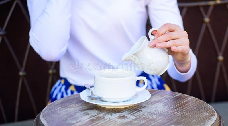 Tipps für das gesündere Kaffeetrinken Kaffee immer besser mit Milch Übergeben Sie weibliche hinzufügende Milch zum schwarzen Kaff stockfotografie