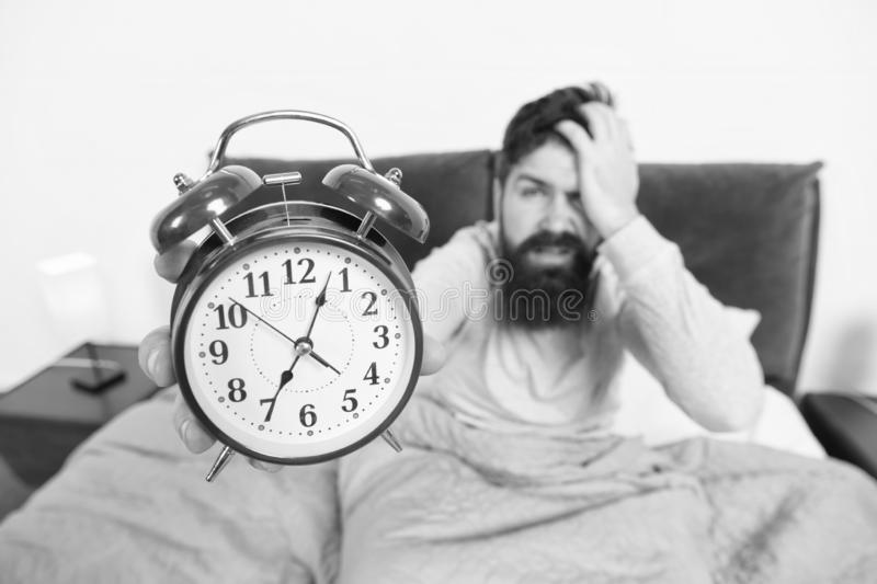 Tips for becoming an early riser. Man bearded hipster sleepy face in bed with alarm clock. Problem with early morning. Awakening. Get up with alarm clock stock photography