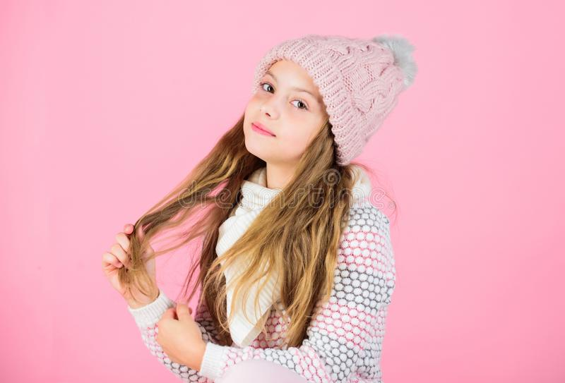 Tips for caring for knitted garments. Child long hair warm soft woolen hat enjoy softness. Kid girl wear knitted soft royalty free stock photo