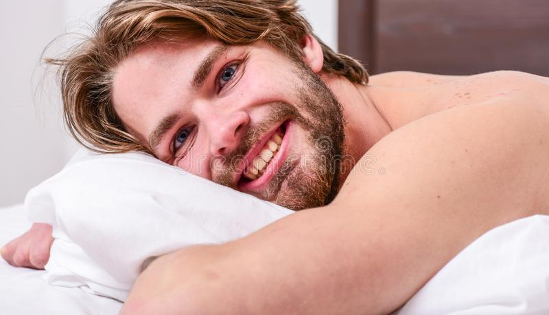Tips on how to wake up feeling fresh and energetic. Morning routine tips to feel good all day. Man handsome guy lay in stock image
