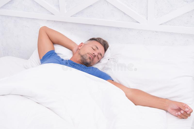 Tips sleeping better. Bearded peaceful man sleeping face relaxing on pillow covered blanket. Total relaxation. Healthy. Habits. Man handsome guy lay in bed stock photography